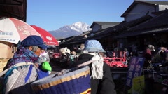 Naxi women carry woven wicker baskets in a market Stock Footage