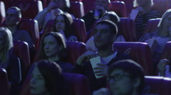 Group of people are scared while watching a horror film screening in a cinema - stock footage