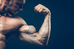 The athlete shows his beautiful body on black background - stock photo