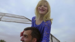 Little girl sits on uncles shoulders Stock Footage