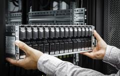 IT Engineer installs JBOD  to rack in datacenter - stock photo
