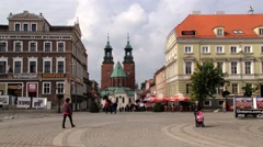 People walk by the central square of the historical town of Gniezno, Poland. Stock Footage