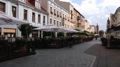 People walk by the street in the historical town of Gniezno, Poland. Stock Footage