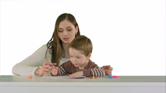 Mom and kid boy painting together on table on white background isolated Stock Footage