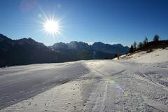 The ski slope with a view on Dolomiti mountains and sun, Madonna di Campiglio Stock Photos