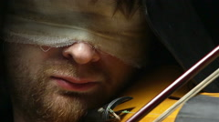 Beard man in hood playing the fiddler Stock Footage