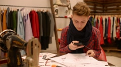 Fashion designer makes photo by sell phone of a new collection of sketches Stock Footage