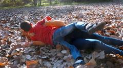 Children fight in autumn park leafs Stock Footage