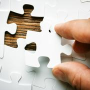 Hand with missing jigsaw puzzle piece. Business concept image for completing - stock photo