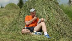 Man in orange t-shirt with tablet PC sits near haystack Stock Footage