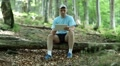 Man with Tablet PC sits on a fallen tree in the forest Footage
