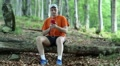 Man with red smartphone sits on a fallen tree in the forest HD Footage