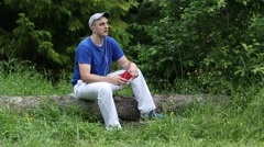 Man with red smartphone sits on a fallen tree in the wood and listens to music Stock Footage