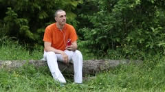 Man with red smartphone sits on a fallen tree in forest and listens to music Stock Footage
