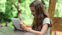 Beautiful girl with white tablet computer sits at the table Stock Footage