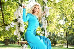 Attractive blond beauty on a flower swing in a park - stock photo