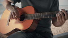 Musician playing guitar on the beach. Close-up of guitar neck and hand. Sunset. Stock Footage