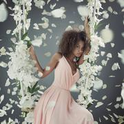 Pretty mulatto woman among white petals - stock photo