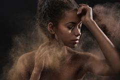 Pretty mulatto woman sprinkling a dust - stock photo