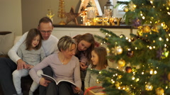 Family reading book at christmas tree Stock Footage