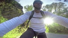 Man Cycling  pov under sun shine on mountain road, camera attached to handleb Stock Footage