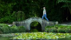 Woman Walks Across Japaneese Garden Bridge Stock Footage
