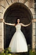 bride stands in the arch of the castle - stock photo