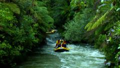 A pair of yellow rafts filled with sportsmen makes it's way down a river over a Stock Footage