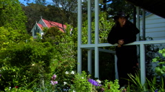 Man on Garden Porch with Church in Background Stock Footage