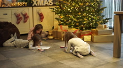 Children playing under christmas tree Stock Footage