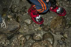 Colorful child's boots on beach Stock Photos