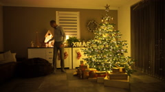 Dad ringing bell in front of christmas tree Stock Footage