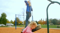 Adorable little girl twirls her older sister on a tire swing Stock Footage