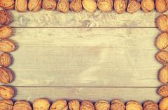 Vintage stylized framed background made of walnuts Stock Photos