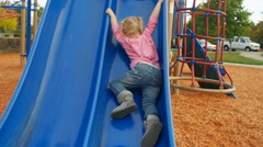 Cute toddler can't seem to make it up the slide Stock Footage