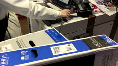 Woman checking price of TV to buy inside Best buy store Stock Footage