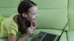 Frightened little girl looks terrible video on laptop Stock Footage