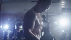 Handsome fit sporty man without shirt does dumbell curl exercises in the gym - stock footage