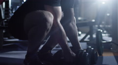 Handsome fit sporty man does dumbell curl exercises in dark gym - stock footage