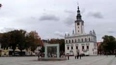 People walk by the square in front of the town hall building in Helmno, Poland. Stock Footage