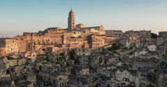 Panoramic view of typical stones and church of Matera under sunset sky Stock Footage