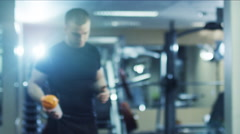 Handsome fit sporty man holds a shaker and poses in the gym - stock footage