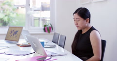 Tired and stressed Asian businesswoman at work. Shot on RED Epic. - stock footage