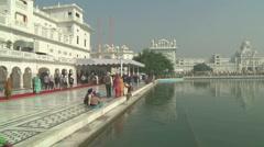 Pan WS of people walking near Harmandir Sahib in Amritsar, India - stock footage