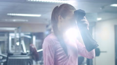 Attractive fit sporty girl is wiping her face with a towel and posing in the gym - stock footage