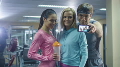 Two girls and a man are making selfie pictures on mobile phone in the gym Stock Footage