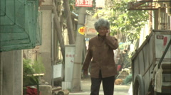 Old Chinese woman in alley, Xiamen, China Stock Footage