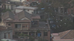 Pigeons flying over rooftops, Xiamen, China Stock Footage