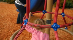 Girl plays in and around the jungle gym - stock footage