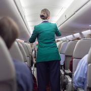 Stewardessand passengers on commercial airplane. - stock photo
